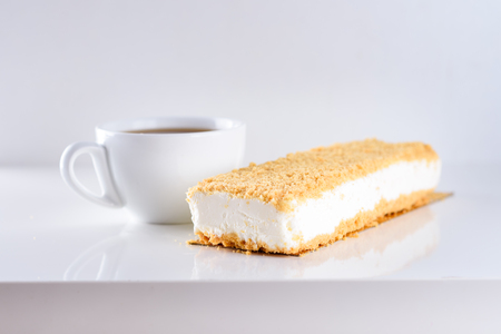 Cheesecake topped with Crumb and cup of coffee on white background-greatest breakfast. White icecream cake on wooden table. Shavuot, holiday, lifestyle, happy moments concept.