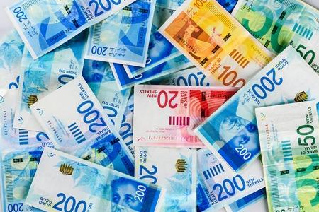 Stos NIS - nowe banknoty izraelskich szekli z nowymi 200, 100, 20, 50 szekelami. Tapeta szekli - widok z góry. Polityka i pieniądze pochodzenia izraelskiego.