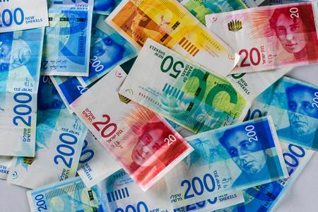 Stack of various Israeli shekel bills. Israel money banknotes of 50, 20, 100 and 200 NIS - New Israeli Shekels background. Top view. Stock Photo