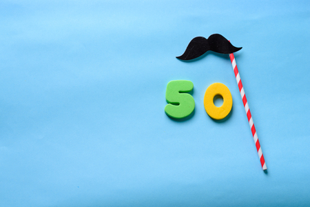 50 celebrating yellow green number with  mustache cute paper mask on straw stick.Fifty Modern alphabet digits on blue background. 50 th birthday party anniversary card.Flat lay, top view.Copy space 版權商用圖片