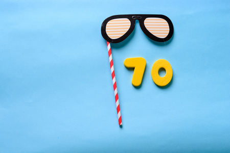 70 celebrating yellow number with sunglasses cute paper mask on stick. Seventy Modern alphabet digits on blue background. 70th birthday party anniversary card.