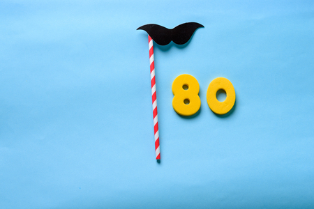 80 celebrating yellow number with  mustache cute paper mask on straw stick . Eighty Modern alphabet digits on blue background. 80 th birthday party anniversary card.Flat lay, top view.Copy space.