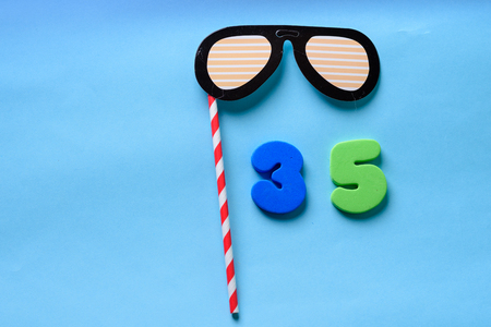 35 celebrating blue green number with sunglasses cute paper mask on straw stick . Thirty five Modern alphabet digits on blue background. 35th birthday party anniversary card.Flat lay, top view. 版權商用圖片
