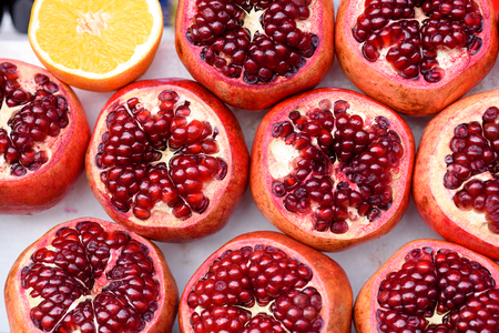 Juicy pomegranates with seed and half fleshy orange. Healthy fruits background.