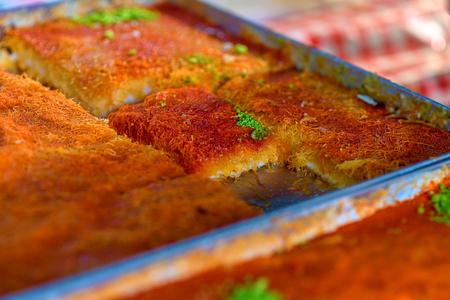 Sweet arab dessert kunefe, kunafa, kadayif with pistachio powder and cheese on the tray in the market.Selective focus. 免版税图像