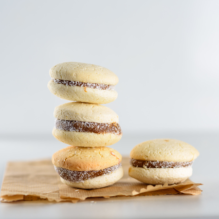Delicious Argentinian cookies alfajores with cream dulce de leche on the table on paper bag, plastic free. Close up white vanilla macaroons on white background. French delicate dessert for breakfast. 版權商用圖片