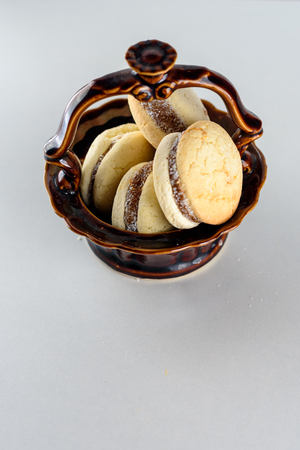 Delicious Argentinian cookies alfajores with cream dulce de leche close-up in a brown ceramic vase. White vanilla macaroons on white background. French delicate dessert for Breakfast.