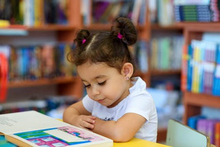 Little Girl Indoors In Front Of Books. Cute Young Toddler Sitting On A Chair Near Table and Reading Book. Child reads in a bookstore, surrounded by colorful books. Library, Shop, Shelving In Home. Archivio Fotografico