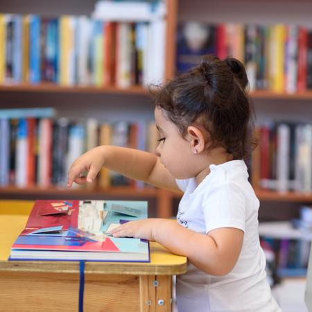 Niña En El Interior Delante De Los Libros. Lindo niño pequeño sentado en una silla junto a la mesa y el libro de lectura. El niño lee en una librería, rodeado de libros coloridos. Biblioteca, tienda, estanterías en casa.