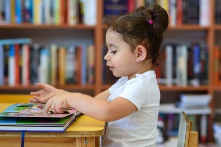 Mała Dziewczynka W Pomieszczeniu Przed Książkami. Cute Młody Maluch Siedzi Na Krześle W Pobliżu Stołu I Czytanie Książki. Dziecko czyta w księgarni, w otoczeniu kolorowych książek. Biblioteka, sklep, regały w domu.