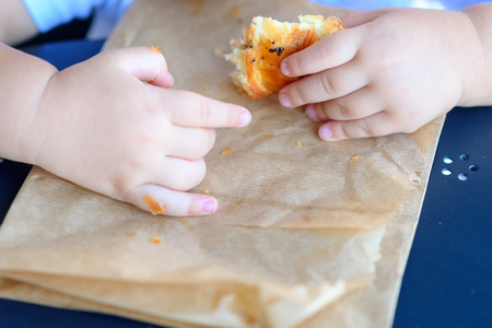Close up hand little cild having breakfast in the cafe on the city street. The child is eating a croissant. Breakfast black table in restaurant eco paper bag.
