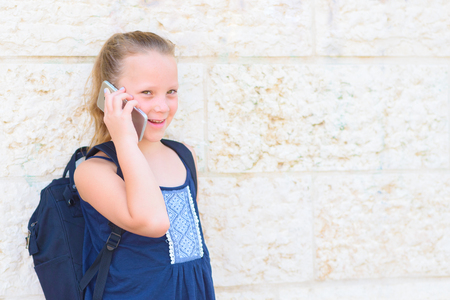 Outdoor portrait of happy girl 8-9 year old talking on phone. Cute schoolgirl with backpack talking on cell phone and smiling.