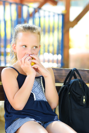 Little girl is eating an apple. Healthy nutrition. Pretty child eating an apple at park , nature outdoors. Teenager pupil enjoying healthy lunch in schoolyard.