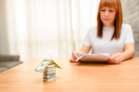 Money house from dollar banknote on wooden table.Happy woman sitting and calculating bills in the home office. Concept of buying a home, real estate activity,looking at new houses for sale.Copy space