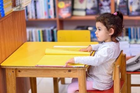 Meisje Binnen Voor Boeken. Schattige jonge peuter zittend op een stoel in de buurt van tafel en leesboek. Kind leest in een boekhandel, omringd door kleurrijke boeken. Bibliotheek, winkel, rekken in huis. Stockfoto