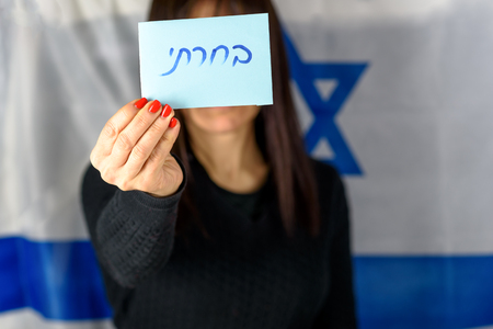 Young Woman Holding Ballot Front Of Face on Israeli Flag Background.Hebrew text I Voted on voting paper.Israel to hold new elections 17 September 2019 after Netanyahu coalition talks fail.