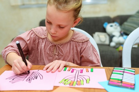 Needlework, crafts children.Little girl create a greeting card image of the Jewish holiday of Hanukkah. Kid pastes stickers - candles and drawing menorah, dreidel, oil jar on paper on wooden table.