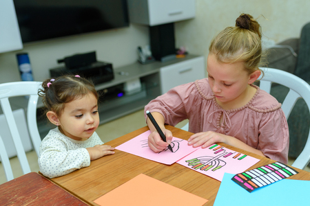 Needlework, crafts children.Little girl create a greeting card image of the Jewish holiday of Hanukkah.Kidd pastes stickers, glue candles and drawing menorah, dreidel, oil jar on paper on wooden table Imagens