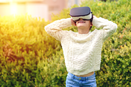 Young beautiful slim teenage girl with dental brace wearing virtual reality glasses in outdoor nature background. Smartphone using with VR goggles headset. Archivio Fotografico