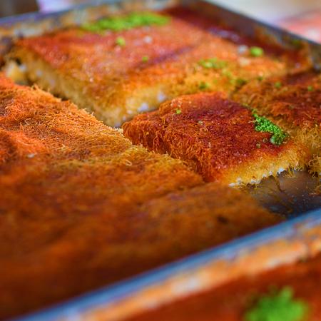 Sweet arab dessert kunefe, kunafa, kadayif with pistachio powder and cheese on the tray in the market.Selective focus. 版權商用圖片