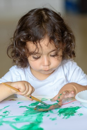 Portrait cute little kid drawing with green paint on fall leaf. Curly adorable child painting at table. Reklamní fotografie