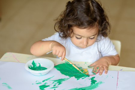 Portrait cute little kid drawing with green paint on fall leaf. Curly adorable child painting at table.