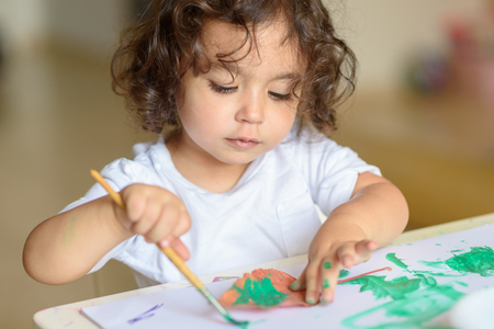 Portrait Cute little girl drawing with green paint on fall lives. Curly adorable child painting at table.
