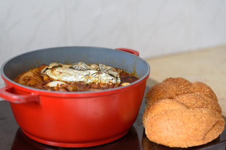 Hot plate for the Sabbath, a pot of spicy meat cooked with potatoes, barleys, wheat and eggs. Pot of cholent Hamin in hebrew, challah-special bread in Jewish cuisine. Traditional food Jewish Shabbat. Stock Photo