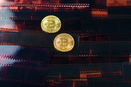 Two cryptocurrency bitcoin over Exposed and Developed old film negative strips background.