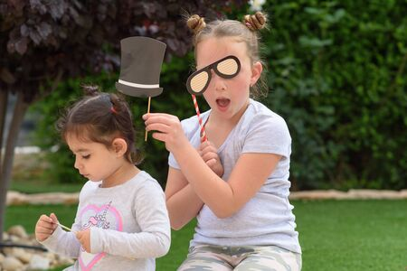 Two funny little girl having fun outdoor. Children have play with carnival paper hat and glasses masks. Props for the party. Stock Photo