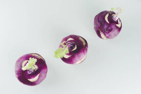 Fresh kohlrabi on white background. Group of raw organic purple turnip cabbage ready to eat.