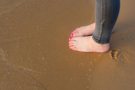 Young Woman foot going on the summer beach. Close up leg of teenager walking along wave of sea water and sand on the beach. Travel Concept in warm climates.Copy space for text.