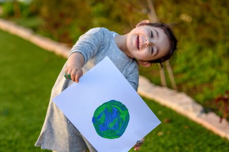 Portrait of the cute little girl holding the drawing earth globe. Child drawnig a picture of earth.