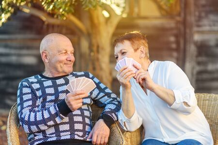 Senior couple playing cards game at park on sunny day. Smiling Elderly Man and Woman have fun in outdoor garden at sunset. Woman laugh and pry into cards of her husband.