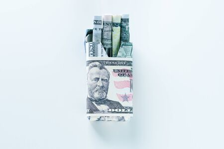 Package of cigarette filled with paper money dollars banknote instead of cigarette sticks. Concept Smoking is actually burning or wasting money .