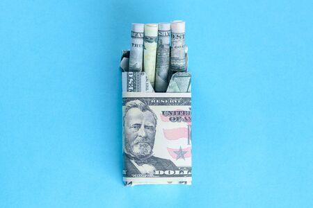 Paquete de cigarrillos lleno de billetes de dólares de papel moneda en lugar de palos de cigarrillos. Concepto Fumar es, en realidad, quemar o desperdiciar dinero.