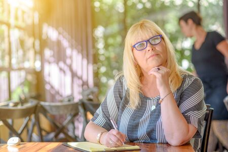 Portrait of beautiful plus size middle age woman working and making notes to her diary on sunny terrace of cafe. Elegant middle aged lady posing with modern glasses.