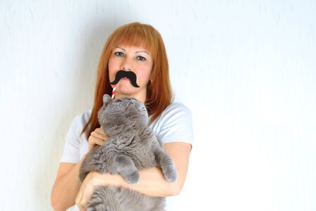 Attractive middle aged woman with cute british shorthair cat resting at home.Mature woman having fun with a fake moustache and embracing pet.A woman in the period of menopause. Selective focus on cat.