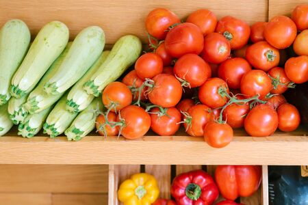 Fresh a variety of vegetables lie on the counter in the store, supermarket or vegan coffee shop. Purchase of tomatoes, zucchini, sweet pepper, vegetables variety.
