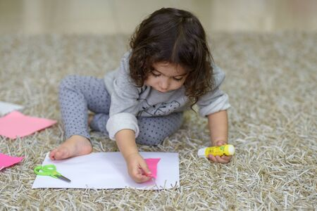 Cute little girl make applique, glues pink , applying a color paper using glue stick while doing arts and crafts in preschool or home. The idea for children's creativity, art project. Stock fotó