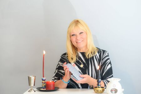 Middle age beautiful woman sits near a fortune teller desk with a Tarot cards and candles. Card reading. Divination and clairvoyance.