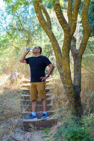 Elderly success athlete senior man drinking water after trip or travel on sunny summer day in forest, antique park. Outdoor portrait mature man tourist,lifestyle, sport, health, retirement concept.