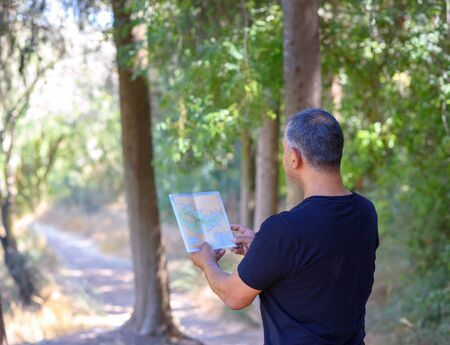 Back side traveler senior man searching right direction on map, sunny day, traveling along nature.Old Tourist with map standing in amazing forest, freedom, active lifstyle, happy and health retirement Imagens