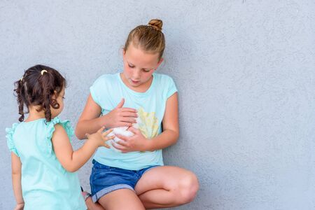 Teenager child holding a cute little white rabbit.Two happy young girls playing with rabbit.