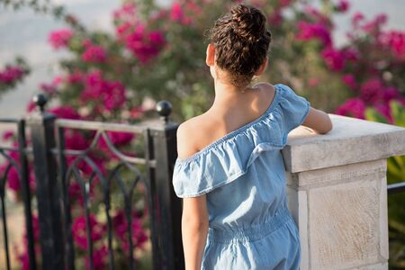Beautiful girl admiring the view in the sunset on sunny day.Back view of young teenager child with hair bun. Archivio Fotografico