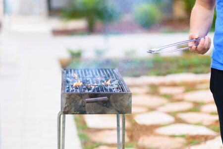 Handsome athlete male prepares barbecue outdoors. Brutal bearded man standing and prepared grill, burn charcoal outdoor with sunset nature summer garden background. Banco de Imagens