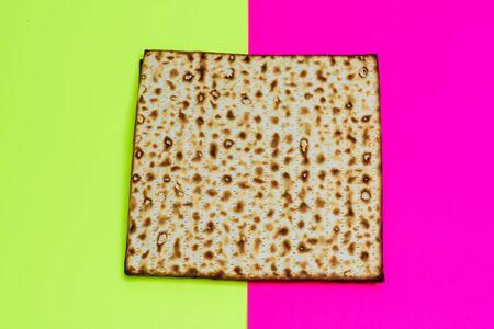 Matzah on bright celebrating background.Matza -Jewish traditional Passover unleavened bread. Pesach celebration symbol.