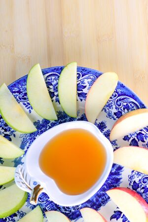 Jewish holiday Rosh Hashana background with honey and slices of apple on wooden table. During the Jewish New Year Rosh Hashanah customary eat sliced apples dipped in honey symbol sweet new year.