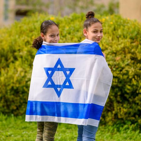 Two patriot jewish teenager girl standing and enjoying with the flag of Israel on nature background. Election, Yom Hazikaron, patriotic holiday Independence day Israel - Yom Haatzmaut concept. Archivio Fotografico