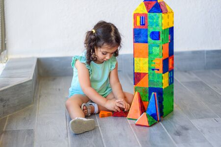 Little girl playing with lots of colorful plastic blocks constructor and builds house. Foto de archivo